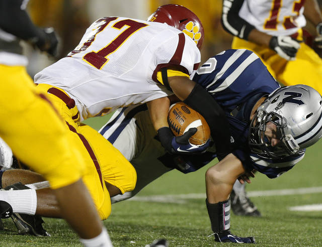 Edmond North's Chad Whiteley is brought down by Putnam City North's Michael Wofford during a high school football game at Wantland Stadium in Edmond, Okla., Friday, September 21, 2012. Photo by Bryan Terry, The Oklahoman