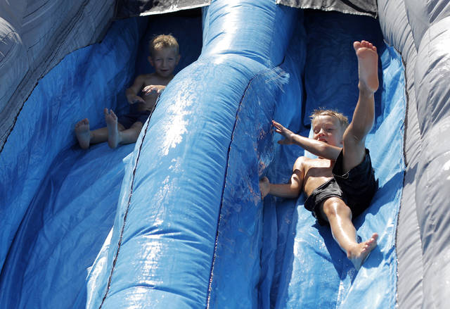 Trey Burden, 5 of El Reno, and Quin McCoy, 5 of Ada, go down a water slide during the International Finals Youth Rodeo, Monday, July 11, 2011.  Photo by Garett Fisbeck, The Oklahoman