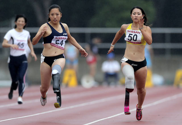 In this photo taken Saturday, July 7, 2012, Paralympic athlete Maya Nakanishi, right, wearing new custom-designed, black and red racing blade, competes with Saki Takakuwa in the women's 100-meter final at the 17th Handicapped Truck and Field Championships in Tokyo. Nakanishi is one of Japan's most promising track and field athletes and is now on her way to the London Olympics. To earn money for two spares of her racing blade, Nakanishi published a calendar with photographs of her in the nude. The calendar earned her about 5 million yen ($50,000). (AP Photo/Itsuo Inouye)