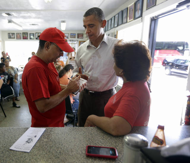 President Barack Obama, center, places his food order with Pedro Barrionuevo, left, and his wife Nidia Barrionuevo, right, owners of West Tampa Sandwich Shop and Restaurant, during an unannounced stop, Saturday, Sept. 8, 2012, in Tampa, Fla. (AP Photo/Pablo Martinez Monsivais)