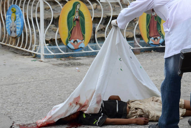 The body of a young man who was shot to death is covered by a forensic officer at the Pacific resort city of Acapulco, Mexico, Tuesday Aug. 23, 2011. The city of Acapulco has been hit by violence as drug gangs continue to battle for control of the region. In background, an image of the Virgin of Guadalupe. (AP Photo/Bernandino Hernandez)