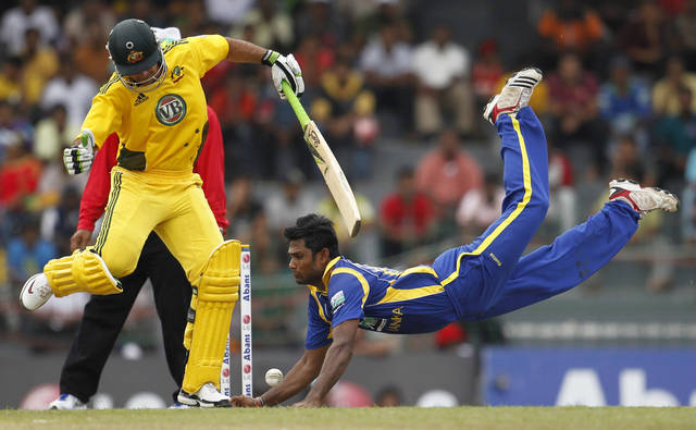 Sri Lanka's bowler Seekkuge Prasanna dives to stop a ball as Australia's batsman Ricky Ponting jumps during the fifth one-day international cricket match between Sri Lanka and Australia in Colombo, Sri Lanka, Monday, Aug. 22, 2011.(AP Photo/ Eranga Jayawardena)