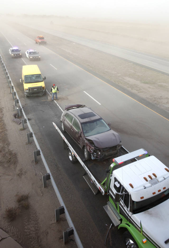 A car is loaded on a wrecker from a 30 car pile up during a dust storm on I-35 between State highway 60 and 11 in far north Oklahoma, Thursday, October 18, 2012. The yellow van was also towed away. Photo By David McDaniel/The Oklahoman