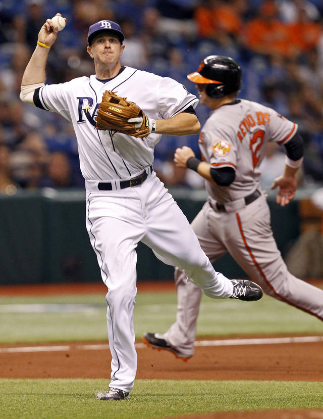 Tampa Bay Rays third baseman Drew Sutton, left, throws wide of first base on a hit by Baltimore Orioles' Robert Andino, allowing Mark Reynolds, right, to score, during the seventh inning of a baseball game on Saturday, June 2, 2012, in St. Petersburg, Fla. (AP Photo/Mike Carlson)