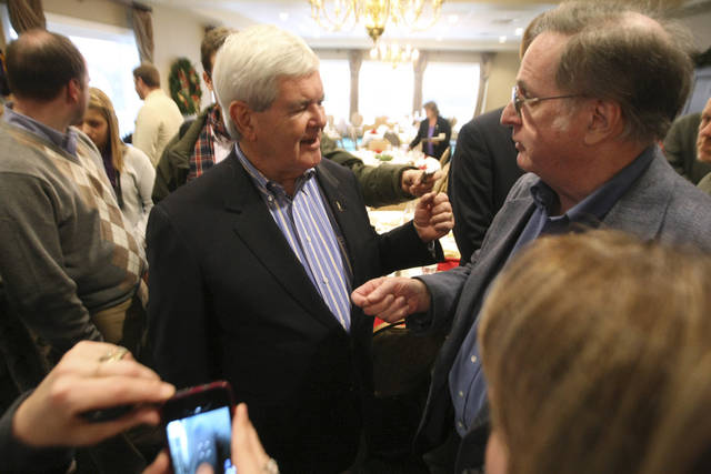 Republican presidential candidate, former House Speaker Newt Gingrich, talks with John Walsh, of Dubuque, Iowa, during a campaign stop at a luncheon meeting of the Dubuque Rotary Club Tuesday, Dec. 27, 2011, at the Dubuque Golf and Country Club in Dubuque. (AP Photo/The Telegraph Herald, Jessica Reilly)