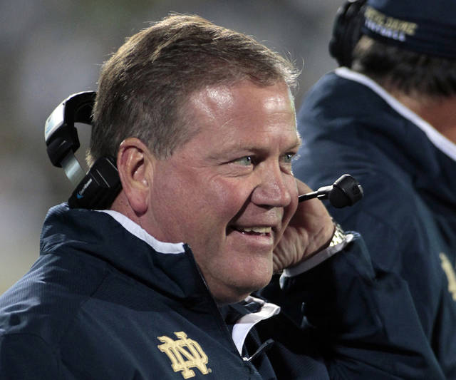 """FILE - In this Sept. 15, 2012, file photo, Notre Dame coach Brian Kelly smiles on the sideline during the first quarter of an NCAA college football game against Michigan State in East Lansing, Mich. Coach Kelly called it """"white noise"""" when Notre Dame jumped into the rankings after its season-opening victory over Navy. That noise is getting harder to ignore now that the Irish are 4-0, ranked No. 9 and every team on their schedule has at least one loss and none is ranked higher than No. 13. (AP Photo/Al Goldis, File)"""