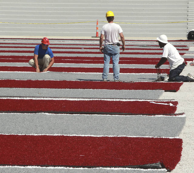 In this June 22, 2012 photo, workers align and stretch the sections of artificial field surface to prep them for the glue process at the football field at Lindenwood University's Belleville, Ill., campus. The university is making its leap into college football this fall and has tackled how to make its program instantly unique with a new turf of alternating maroon and gray stripes that's drawing some ridicule. The Lynx's new field is part of a $2.3 million stadium renovation and makes the NAIA program among just a few college football schools nationwide with turf that's a departure from the traditional green. (AP Photo/Belleville News-Democrat, Tim Vizer)