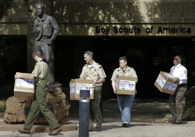 FILE - In this Feb. 4, 2013, photo Eagle Scout Will Oliver, from left, former Scoutmaster Greg Bourke, former den leader Jennifer Tyrrell and Eric Andresen, right, a parent of a gay scout deliver boxes filled with a petition to the statue in front of the Boy Scouts of America headquarters in Irving, Texas. The Boy Scouts of America&#039;s policy excluding gay members and leaders could be up for a vote as soon as Wednesday, when the organization&#039;s national executive board meets behind closed doors under intense pressure from several sides. (AP Photo/Tony Gutierrez, File)
