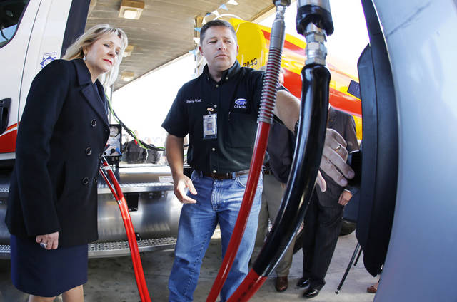 "Gov. Mary Fallin, left, watches Gemini Motor Transport driver Robert Felts demonstrate how to fill his truck with compressed natural gas Monday during the opening of Love's Travel Stops first ""fast fill"" CNG facility for heavy-duty trucks at Interstate 40 and Morgan Road in Oklahoma City. Photo By Steve Gooch, The Oklahoman <strong>Steve Gooch</strong>"