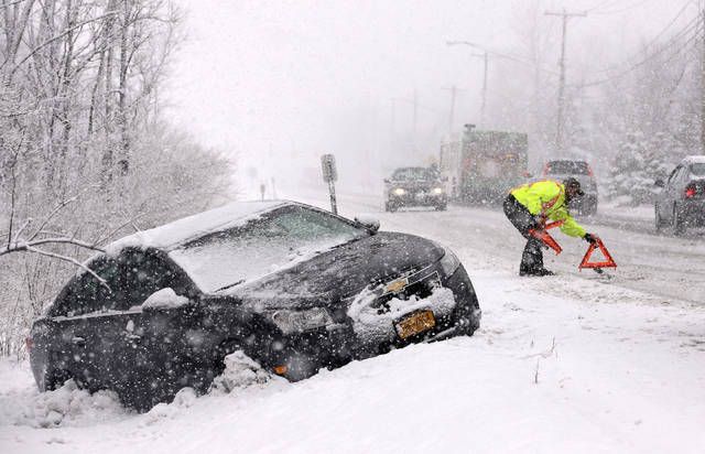 Tow truck operator Shawn Juhre sets up road safety reflectors before towing a car out of a ditch during a winter snow storm in Buffalo, N.Y., Friday, Feb. 8, 2013. Snow began falling across the Northeast on Friday, ushering in what was predicted to be a huge, possibly historic blizzard and sending residents scurrying to stock up on food and gas up their cars. The storm could dump 1 to 3 feet of snow from New York City to Boston and beyond. (AP Photo/David Duprey) ORG XMIT: NYDD106