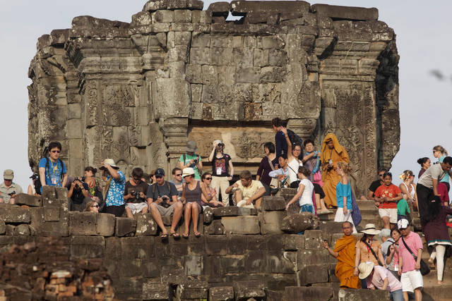 FILE - In this file May 11, 2011, tourists gather on the top of the 10th century temple Bakheng in the Angkor Wat complex near Siem Reap, Cambodia, to view the setting sun. Prime Minister Hun Sen says Cambodia can earn $5 billion a year from tourists by more than doubling foreign visitors to 7 million by 2020. Hun Sen told a tourism seminar Thursday, Sept. 20, 2012, that Cambodia would need to improve the quality of services and infrastructure for tourists and strengthen laws safeguarding them to achieve the goal. (AP Photo/David Longstreath, File)