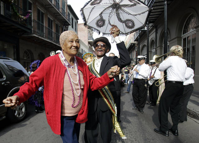 FILE - In this Feb. 17, 2006 file photo, Uncle Lionel Batiste, center with umbrella, dances with an unidentified woman who danced in from the sidewalk during the Krew of Cork parade through New Orleans' French Quarter. Batiste, the vocalist, bass drummer and assistant band leader of the Treme Brass Band, has died. He was 81. Band leader Benny Jones Sr. says Batiste died Sunday, July 8, 2012. (AP Photo/Carolyn Kaster, File)