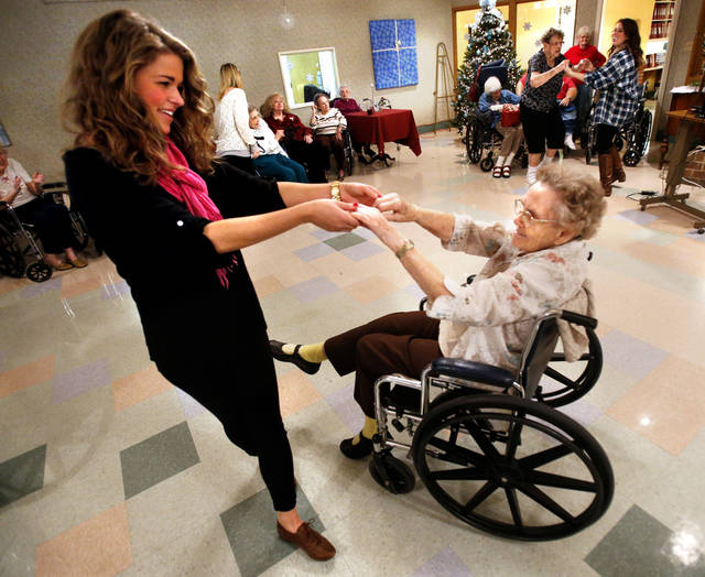 Kappa Alpha Theta sorority member Kirby Olson invites Grace Living Center resident Christine Ernest to dance at a party organized by members of the University of Oklahoma sorority.