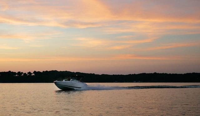 A boat powers across Grand Lake as the sun sets. By Nate Billings, The Oklahoman Archives <strong>NATE BILLINGS - THE OKLAHOMAN</strong>