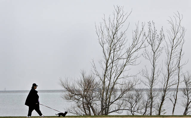Seen against the grey sky, a pedestrian walks a dog along the path around Lake Hefner on Monday, March, 28, 2011, in Oklahoma City, Okla. Photo by Chris Landsberger, The Oklahoman