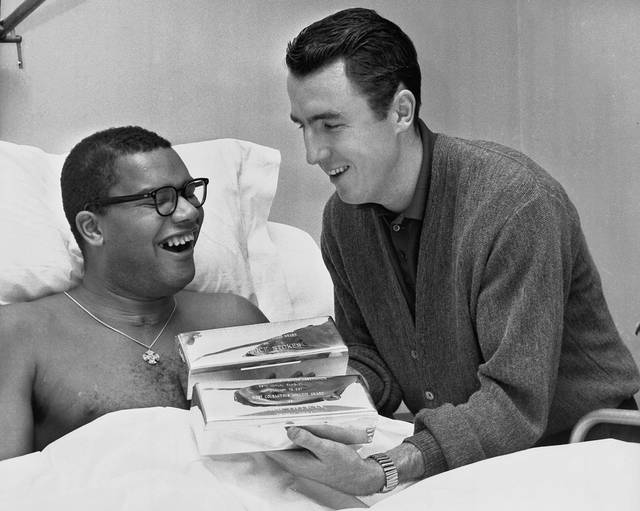 "FILE - In this Feb. 9, 1962 file photo, Jack Twyman, right, holds the trophies he and Maurice Stokes received from the Philadelphia Sports Writers Association designating them as the ""Most Courageous Athletes"" in Stokes' hospital room in Cincinnati, Ohio. Twyman, a Basketball Hall of Famer, has died at 78. He was one of the NBA's top scorers in the 1950s who became the guardian to paralyzed teammate, Stokes. Jay Twyman, of Rye, N.Y., said Thursday, May 31, 2012 that his father died Wednesday, May 30 at a Cincinnati hospice of complications from an aggressive form of blood cancer. Jack Twyman played for the University of Cincinnati and spent 11 seasons in the NBA with the Rochester and Cincinnati Royals. (AP Photo)"