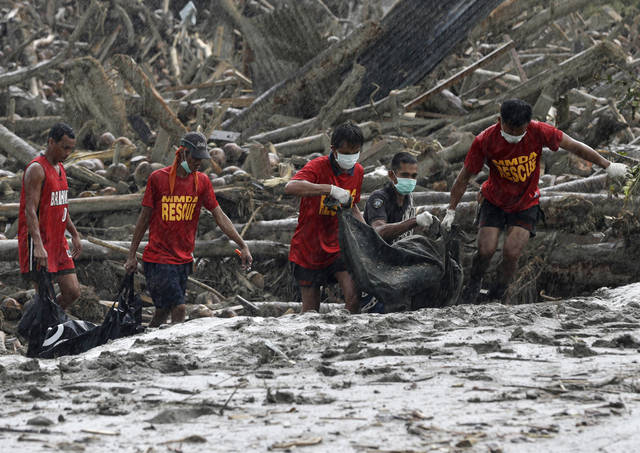Rescuers retrieve flash flood victims from the debris of Tuesday's Typhoon Bopha at New Bataan township, Compostela Valley in southern Philippines Friday Dec. 7, 2012. Rescuers were digging through mud and debris Friday to retrieve more bodies strewn across a farming valley in the southern Philippines by a powerful typhoon. (AP Photo/Bullit Marquez)
