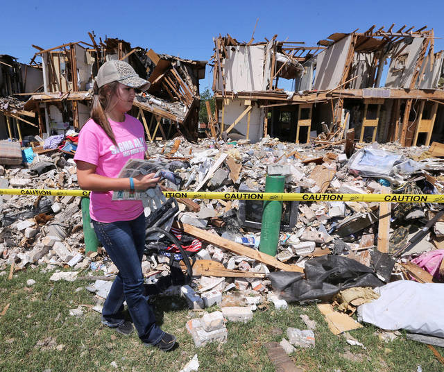 Texas A&M University freshman Heather Warfield collects baseball cards Saturday from an apartment complex in West, Texas, that was damaged in the explosion at a fertilizer plant there on April 17. More than 124 students donated their time to help clean up. AP Photo