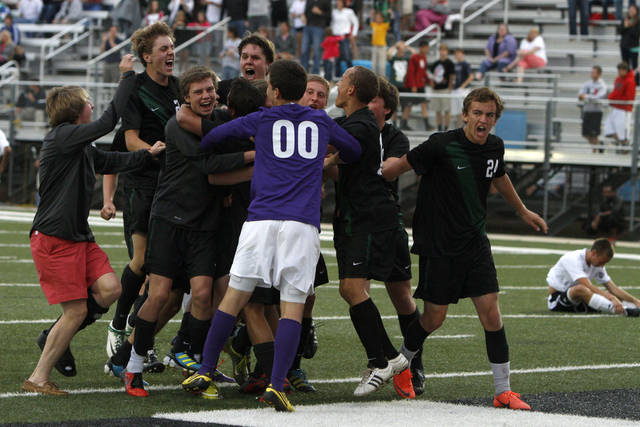 The Norman North team celebrates as Tulsa Union's J.B. Browne, at right, sits on the ground after North's win in the boys 6A state championship soccer game in Newcastle, Okla., Saturday, May 12, 2012. Photo by Bryan Terry, The Oklahoman