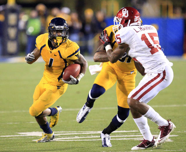 West Virginia's Tavon Austin (1) carries the ball as J.D. Woods (81) blocks Oklahoma's Aaron Colvin (15) during the fourth quarter of their NCAA college football game against Oklahoma in Morgantown, W.Va., on Saturday, Nov. 17, 2012. Oklahoma won 50-49. (AP Photo/Christopher Jackson)