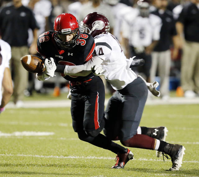 Mustang's AJ Breasette makes a catch but loses the ball on a hit by Memorial's Kourtney Williams at the close of the first half as Edmond Memorial plays Mustang in high school football on Thursday, Oct. 10, 2013, in Mustang, Okla. Photo by Steve Sisney, The Oklahoman