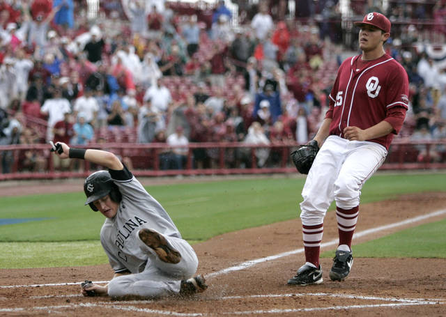 South Carolina's Tanner English, left, scores on a wild pitche by Oklahoma's Steven Okart (15)  in the seventh inning of an NCAA college baseball tournament super regional game in Columbia, S.C., Monday, June 11, 2012. (AP Photo/Mary Ann Chastain) ORG XMIT: SCMC105