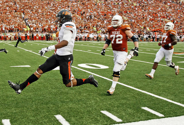 Oklahoma State's Justin Gilbert (4) returns an interception for a touchdown in front of UT's Mason Walters (72) and Kennedy Estelle (77) in the second quarter during a college football game between the Oklahoma State University Cowboys (OSU) and the University of Texas Longhorns (UT) at Darrell K Royal - Texas Memorial Stadium in Austin, Texas, Saturday, Nov. 16, 2013. Photo by Nate Billings, The Oklahoman