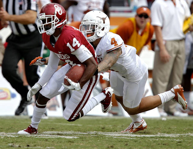 OU's Jalen Saunders (14) is brought down by UT's Kenny Vaccaro (4) during the Red River Rivalry college football game between the University of Oklahoma (OU) and the University of Texas (UT) at the Cotton Bowl in Dallas, Saturday, Oct. 13, 2012. Photo by Chris Landsberger, The Oklahoman