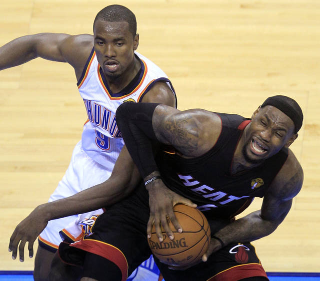 Miami Heat small forward LeBron James  is defended by Oklahoma City Thunder power forward Serge Ibaka (9) from Republic of Congo during the first half at Game 2 of the NBA finals basketball series, Thursday, June 14, 2012, in Oklahoma City. (AP Photo/Sue Ogrocki)  ORG XMIT: NBA139