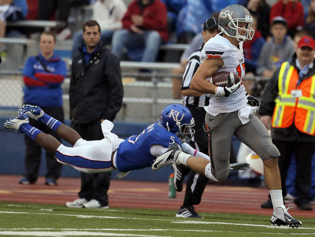 Oklahoma State's Charlie Moore (17) gets by Kansas' Greg Brown (5) as he scores a touchdown during the college football game between Oklahoma State University (OSU) and the University of Kansas (KU) at Memorial Stadium in Lawrence, Kan., Saturday, Oct. 13, 2012. Photo by Sarah Phipps, The Oklahoman