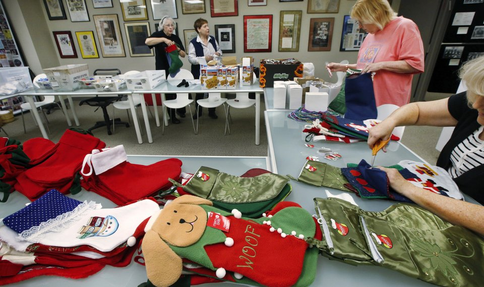 volunteers stuff christmas stockings with small gift items as part of the jewish federation of greater