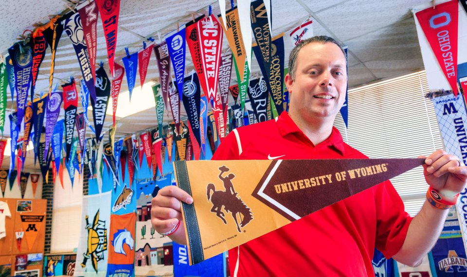 Yukon Middle School sixth-grade geography teacher Daniel Griswold shows some of the college swag he has collected to inspire his students to pursue higher education. [Photo by Chris Landsberger, The Oklahoman]