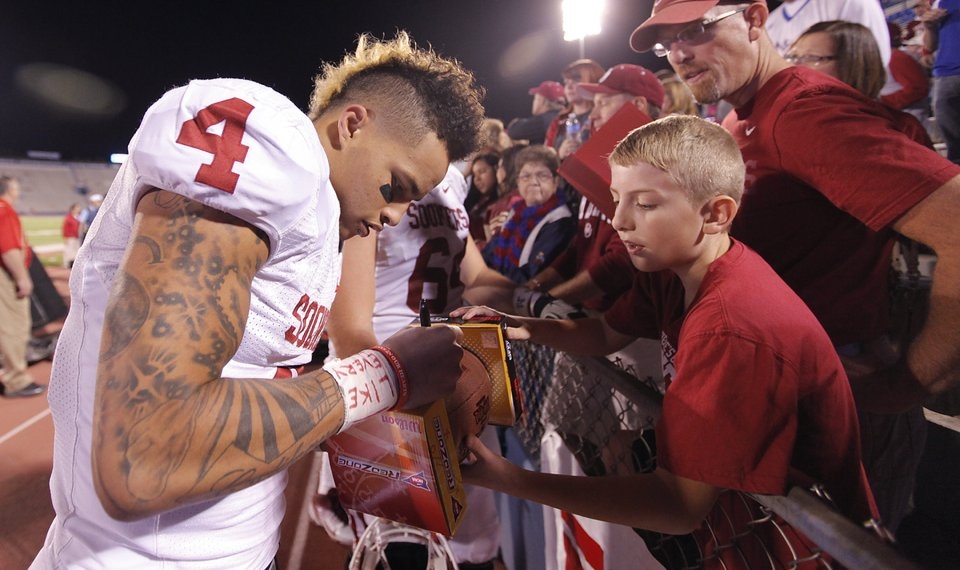 3ebc0f77f12 Oklahoma s Kenny Stills (4) signs autographs for fans during the college  football game between