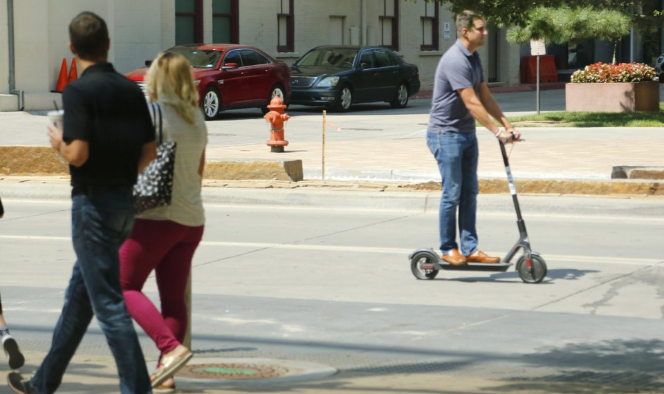 A Person Riding Bird Scooter On Friday Motors North Robinson Avenue In Downtown Oklahoma