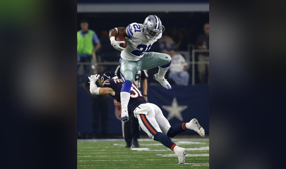Dallas Cowboys running back Ezekiel Elliott leaps over a tackle attempt by  Chicago Bears  Chris f63dd779f
