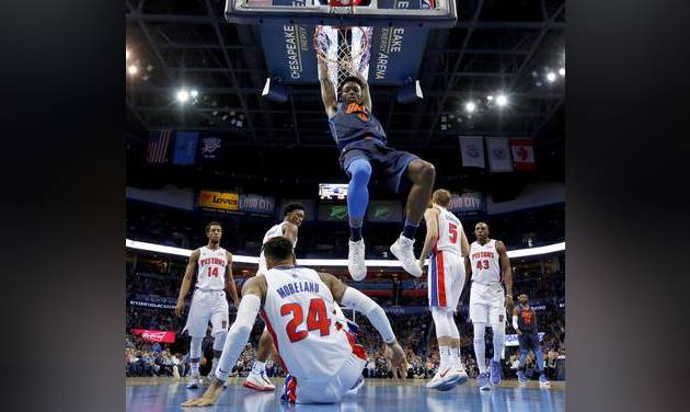 Oklahoma City\'s Jerami Grant, center, dunks the ball during Friday night\'s game against...