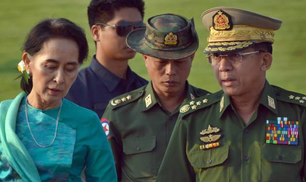 Myanmar's foreign minister and de facto leader, Aung San Suu Kyi, left, walks with Commander-in-Chief of the Myanmar Armed Forces General Min Aung Hlaing, right, in the airport of capital Naypyitaw, Myanmar, Friday, May 6, 2016. Suu Kyi and Myanmar's president Htin Kyaw left Myanmar on a one-day official visit to Laos, their first overseas tour since taking over power in March 2015. (AP Photo/Aung Shine Oo)