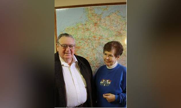 Claus and Helga Greiner in front of a map of Germany in the German American Society of Tulsa Center.  STAFF PHOTO BY DAVID CHRISTOPHER