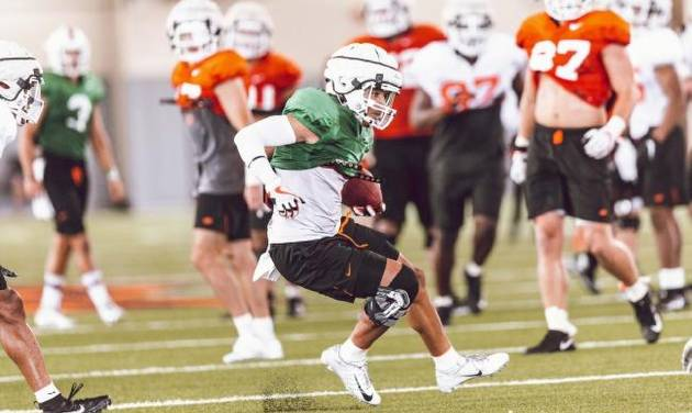 Oklahoma State receiver Tylan Wallace, wearing a brace on his right knee, runs with the ball during practice Friday at the Sherman Smith Training...
