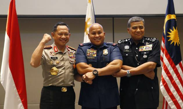 Indonesian National Police Chief Tito Karnavian, left, Philippine National Police Chief Ronald Dela Rosa, center, and Royal Malaysia Police Inspector General Khalid Abu Bakar link arms together prior to the start of their Trilateral Security Meeting in suburban Pasay city, southeast of Manila, Philippines Thursday, June 22, 2017. The Philippines, Indonesia and Malaysia plan to closely cooperate to halt the flow of militants, weapons, funds and extremist propaganda across their borders as they expressed alarm over recent attacks in their countries. (AP Photo/Bullit Marquez)