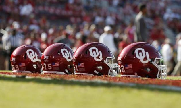 OU helmets sit on the field as players warm up before a college football game between the Oklahoma Sooners (OU) and South Dakota Coyotes at...