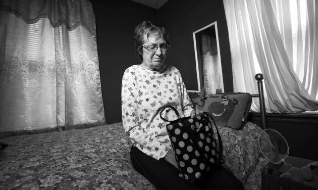Sue Martin sits in the room of her deceased daughter, Lorra Hilton, holding Hilton\'s purse, at...