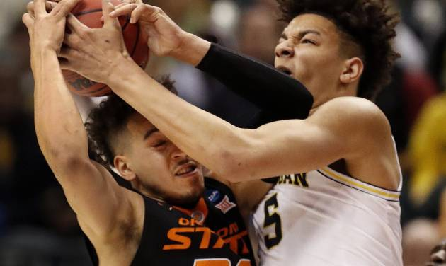 Oklahoma State's Jeffrey Carroll left and Michigan's D.J. Wilson battle for a rebound during the first half of a first-round game in the men's NCAA college basketball tournament Friday