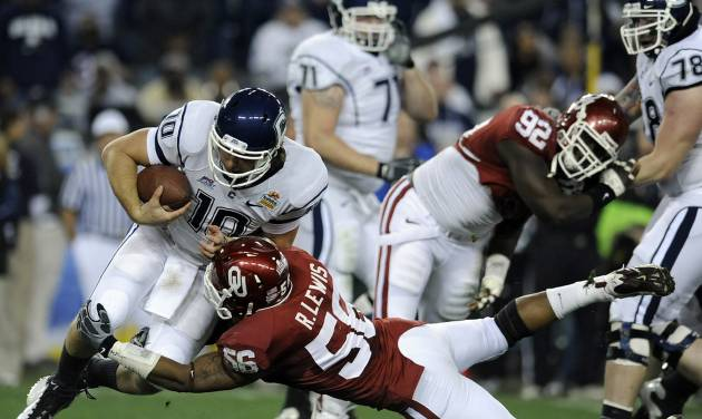 Connecticut's Zack Frazer is sacked by Oklahoma's Ronnell Lewis during the first quarter of the Fiesta Bowl NCAA college football game Saturday,...