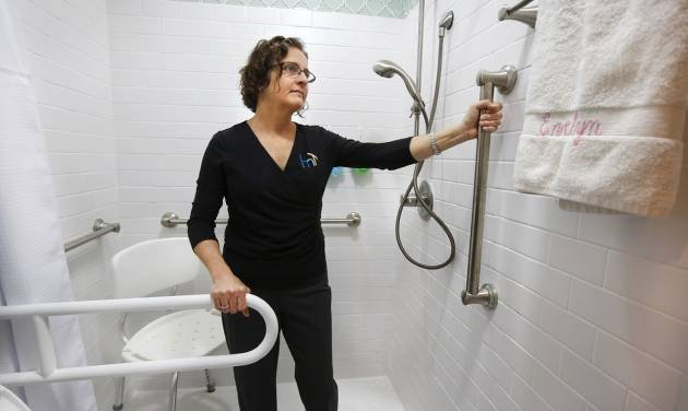 Kendra Orcutt demonstrates features in a new master bathroom she modified. [PHOTO BY JIM BECKEL, THE OKLAHOMAN]