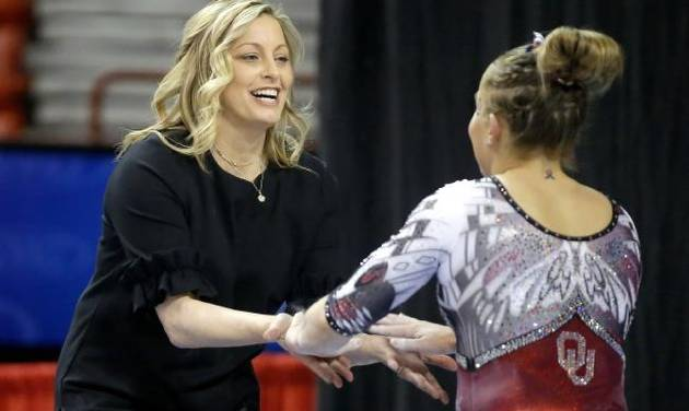 OU women's gymnastics coach K.J. Kindler greets Olivia Trautman after Trautman's balance beam performance during the Perfect 10 Challenge meet...
