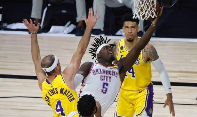 Thunder guard Luguentz Dort drives to the basket in a sea of Lakers, including former OKC Blue guard Alex Caruso (4) during the second quarter...