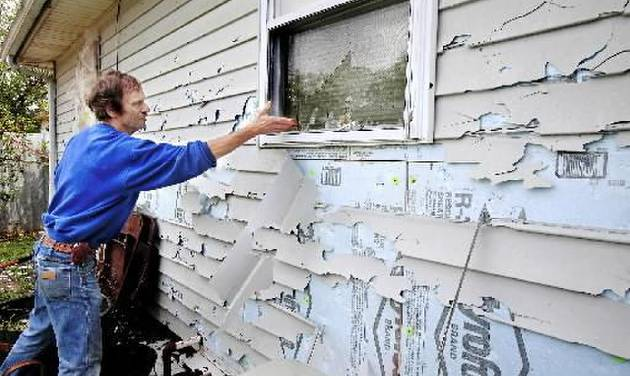 Homeowner Gene Maynard shows the extensive damage to the windows and vinyl siding of his Oklahoma City house in this May 2010 photo by Jim Beckel. The devastating hailstorm is cited as one of the reasons for Oklahoma City's sales tax growth rate.