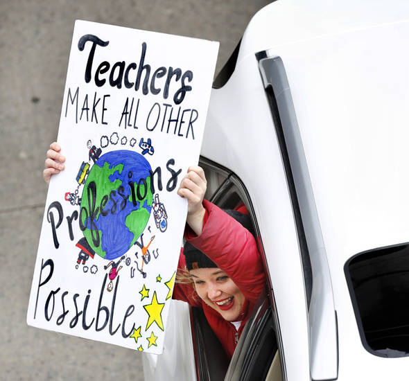 A passenger in a vehicle traveling on NE 23 Street shouts her support and shows her sign to striking teachers standing on an overpass on the north side of the Capitol. Teachers from throughout the state converged at the Capitol to bring their concerns about education funding to the attention of legislators and state officials during the first day of a statewide public schools teacher walkout  on Monday, April 2, 2018. Photo by Jim Beckel, The Oklahoman