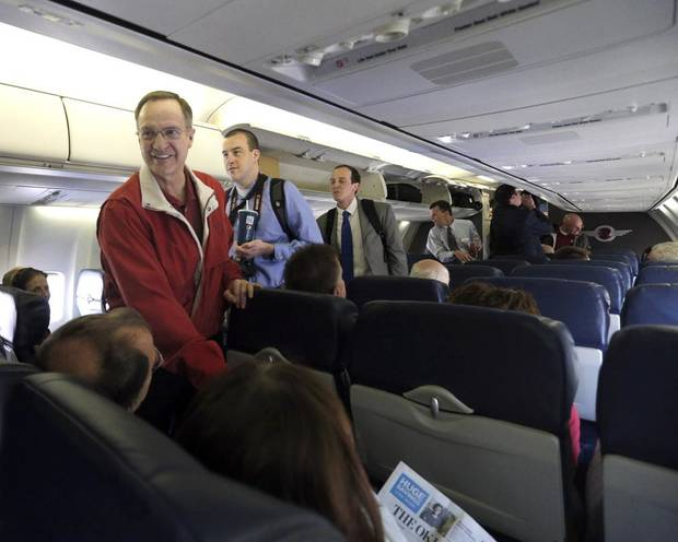 Oklahoma coach Lon Kruger greats guest aboard a plan on the way to Spokane, Wash., for the men's NCAA basketball championship tournament, Tuesday, March 18, 2014.Photo by Sarah Phipps, The Oklahoman